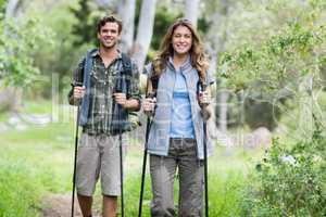 Happy hikers walking with poles in forest