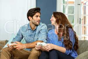 Young couple playing video game while sitting on sofa