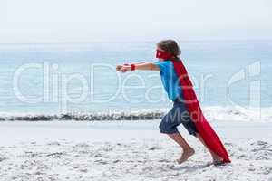 Boy in superhero costume running with clenched fist