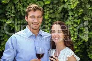 Happy couple holding wineglasses at front yard