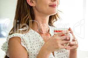 Mid section of woman holding cup of coffee