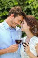 Couple holding wineglasses with eyes closed at front yard