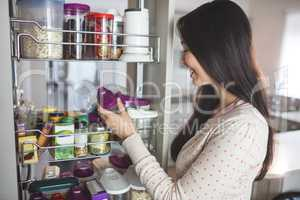 Young woman picking a bottle from storage cabinet