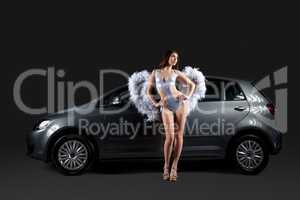 Sexy young girl in angel costume posing near car