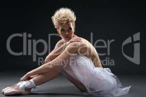 Shot of curly blonde ballerina posing in studio