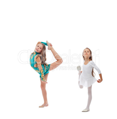 Two cute artistic gymnasts warming up in studio