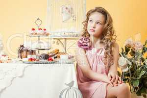 Thoughtful little lady posing at table with cakes