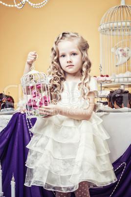 Smart little girl posing in cozy decorated studio