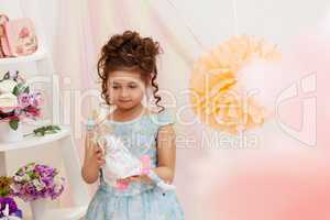 Portrait of smart curly girl posing with doll