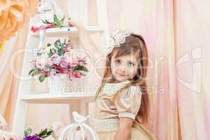 Cute little gray-eyed model posing in cozy studio