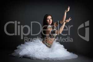Beautiful belly dancer posing in studio