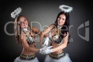 Charming smiling belly dancers posing at camera