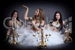 Charming belly dancers posing with chandeliers