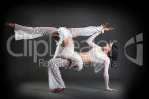 Duet of flexible slim dancers posing in studio