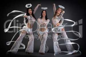 Lovely young women dancing with ribbons in studio