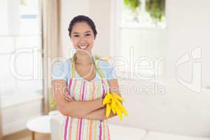 Composite image of woman holding gloves and wearing an apron
