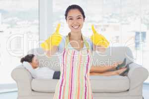 Composite image of happy woman giving thumbs up in rubber gloves
