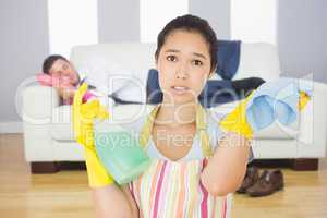 Composite image of weary woman with spray bottle and rag