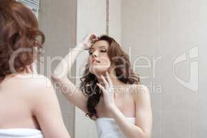 Beautiful girl admires her reflection in mirror