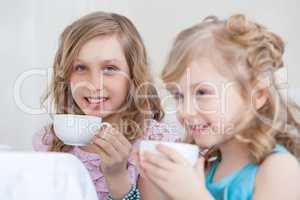 Studio shot of happy little girls drinking tea
