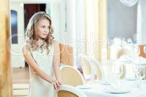 Shy smart girl posing at table in restaurant