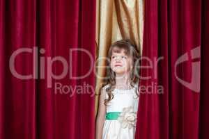 Pretty little brunette posing on curtain backdrop