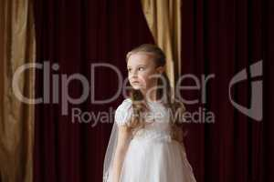 Girlie in white dress posing on curtain backdrop