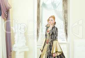 Charming young woman posing in deluxe king costume