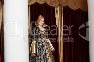 Actress in royal dress posing on curtain backdrop