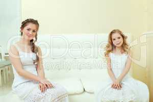 Lovely elegant sisters sitting on white couch
