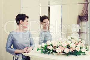 Cheerful middle aged woman laughing in mirror