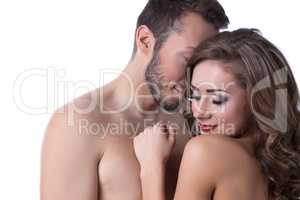 Sexy naked girl shyly hiding in arms of lover