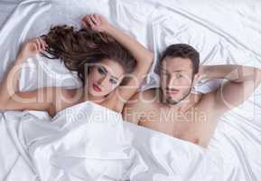 Image of young heterosexual couple posing in bed