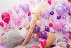 Nude blonde posing with balloons and teddy bear