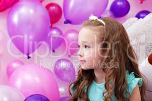 Beautiful little girl on background of balloons
