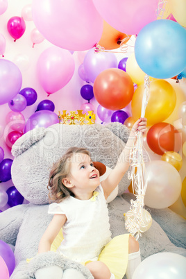 Cheerful little girl grabs bunch of balloons