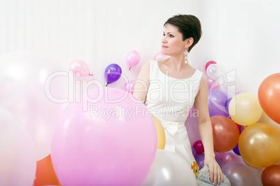 Elegant woman posing among colorful balloons