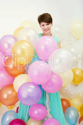 Pretty woman holds big bunch of colorful balloons