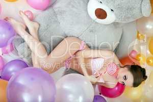 Playful model lying with lollipop on teddy bear