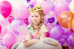 Lovely curly girl posing in crown with lollipop