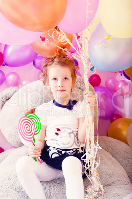 Funny girl holding lollipops and bunch of balloons