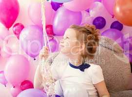 Sympathetic little girl holding bunch of balloons