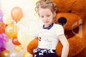 Cute girl posing in embrace with big teddy bear