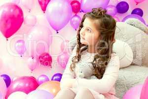 Image of dreamy little girl hugging teddy bear