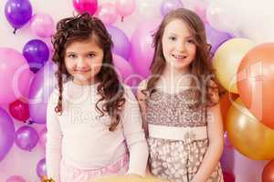 Two merry girlfriends posing on balloons backdrop