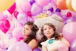 Dreamy sisters posing lying on big teddy bear