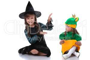 Cute sisters posing in costumes of witch and frog