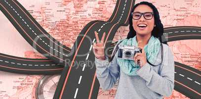 Composite image of asian woman holding digital camera and making