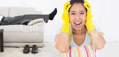 Composite image of distressed woman wearing apron and rubber glo