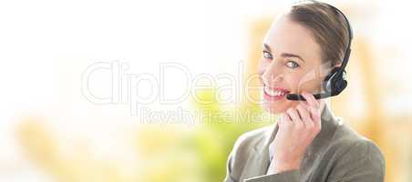 Composite image of smiling businesswoman with headset using comp